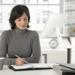 Young woman writing into personal organizer at home