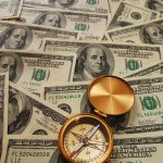 bigstockphoto_Antique_Compass_Over_Money_1726479